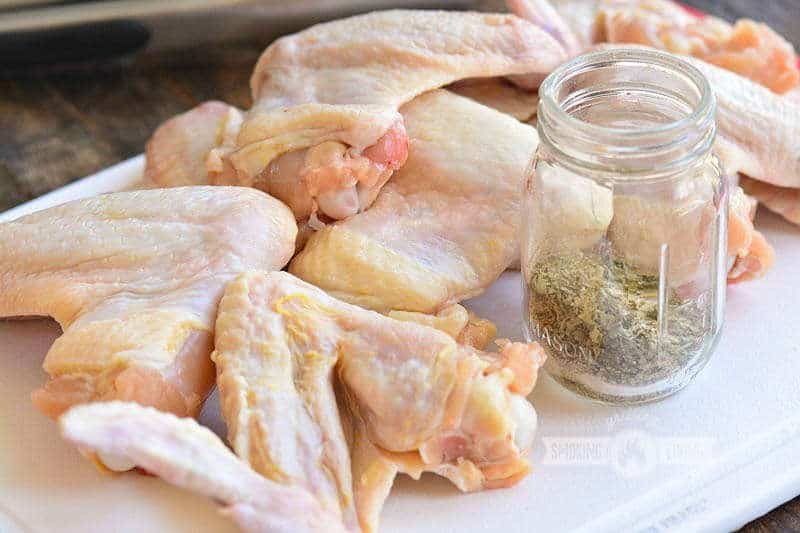 raw wings on the cutting board with seasoning in a jar