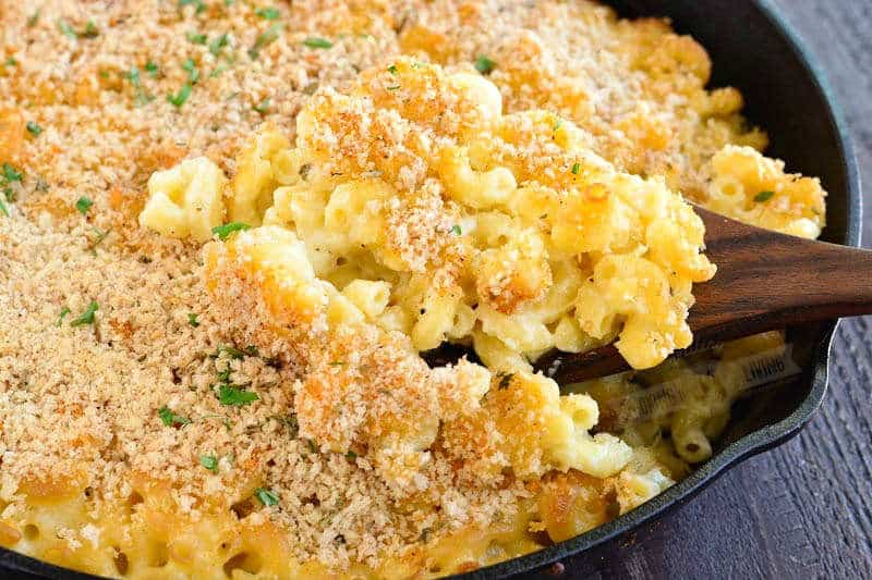 scooping cooked mac and cheese from the skillet