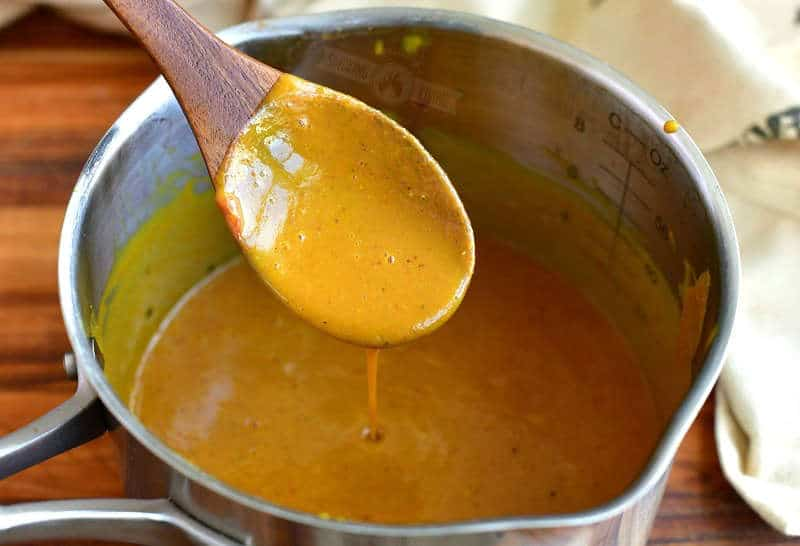 spooning mustard based sauce with a wooden spoon out of a metal sauce pot