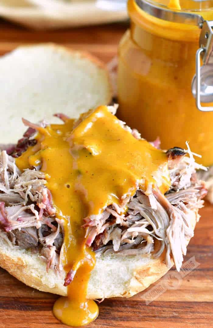 golden sauce poured on top of pulled pork sandwich with a jar of sauce next to it
