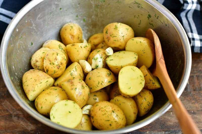 uncooked potatoes tossed with melted butter and dill weed and garlic cloves in a metal bowl