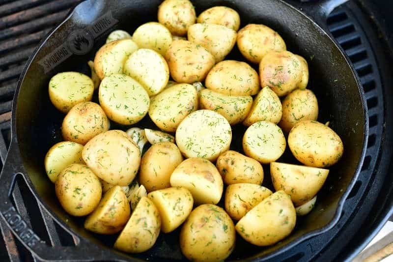 uncooked gold potatoes and garlic cloves coated with dill weed and butter in a skillet on the grill