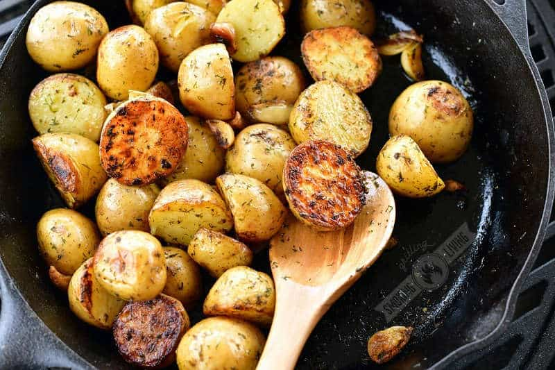 crispy cooked potatoes in the black skillet with wooden spoon and potato half on it