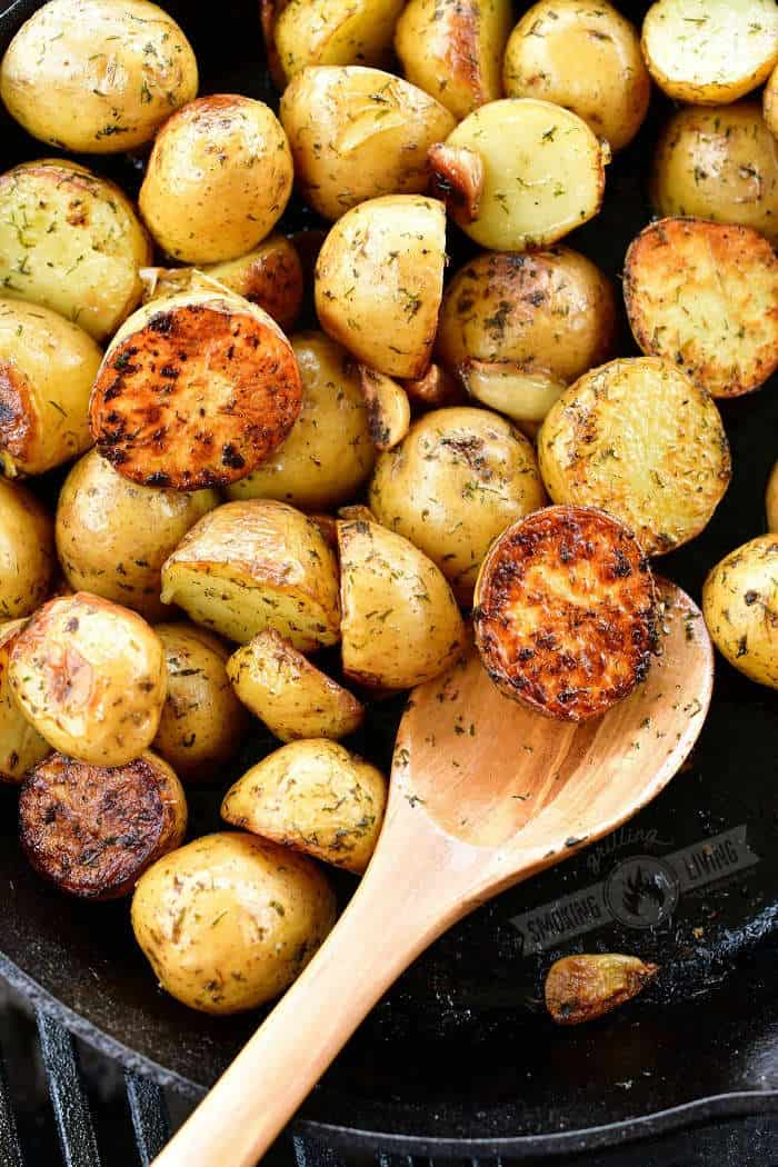 wooden spoon scooping grilled crispy potatoes from the skillet