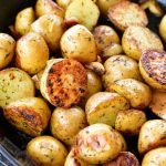 crispy cooked gold potatoes in the skillet on the grill
