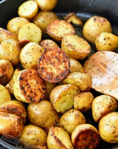 crispu halves of gold potatoes and wooden spoon in the skillet