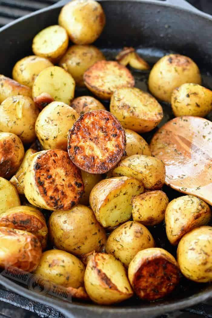 crispy grilled potatoes in a cast iron skillet with a wooden spoon in it