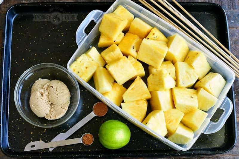 cut chunks of pineapple in a plastic container with lime, brown sugar, cinnamon, and cayenne pepper next to it in a black metal tray