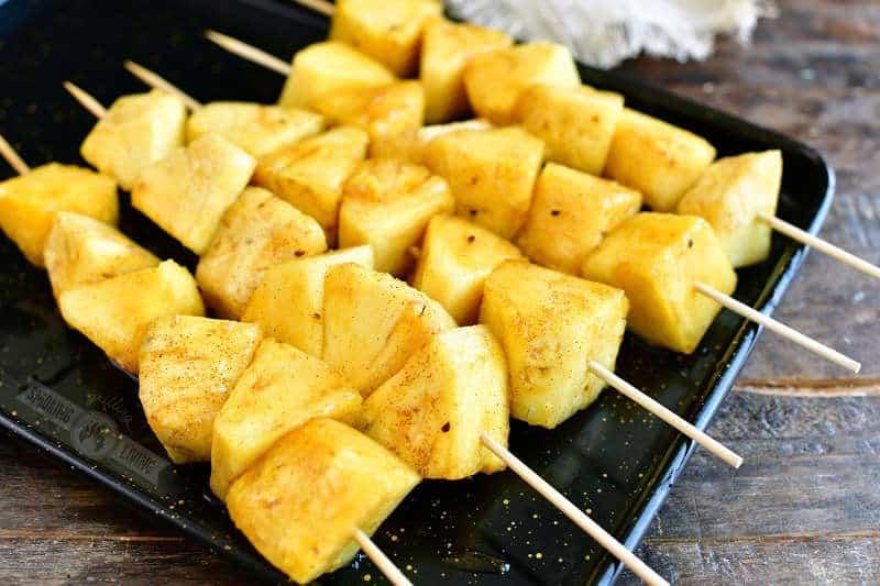 pineapple pieces coated in sugar mixture on skewers on a black metal sheet
