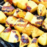 pineapple chunks on skewers on the grill