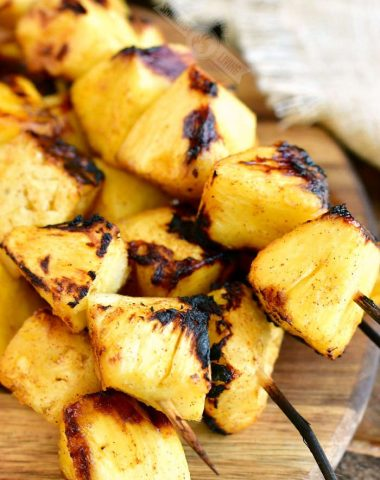 skewers of grilled pineapple chunks on a wooden board