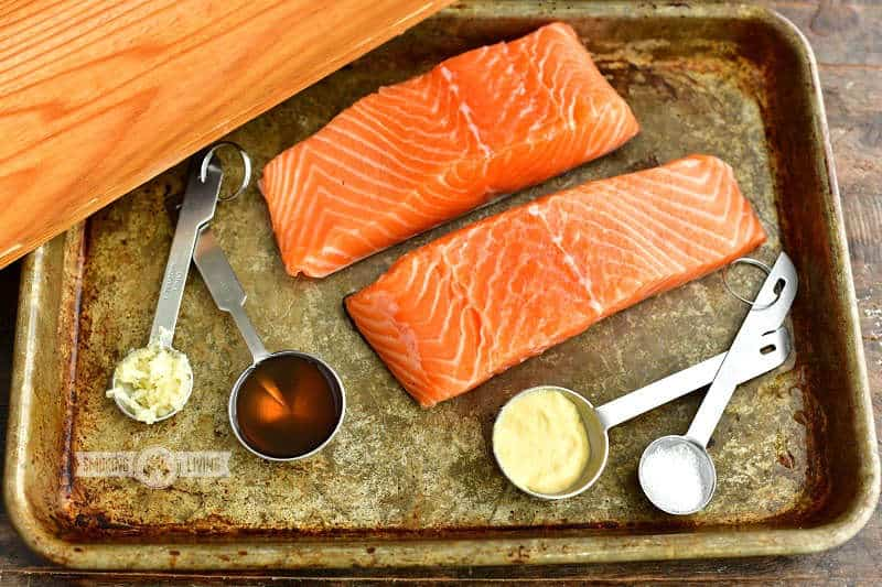 ingredients for the cedar plank salmon on a metal sheet tray: two pieces of salmon, Dijon mustard, salt, maple syrup, pressed garlic and a cedar wood plank