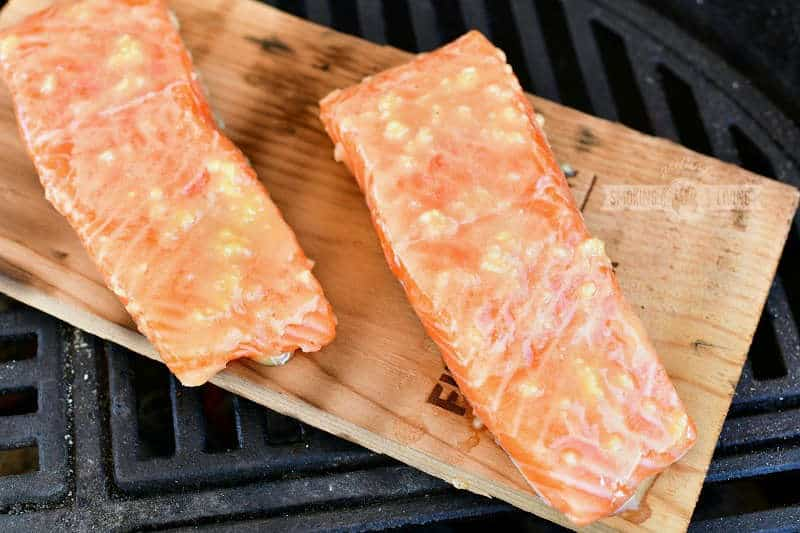 uncooked salmon covered in sauce on a wood plank on the grill