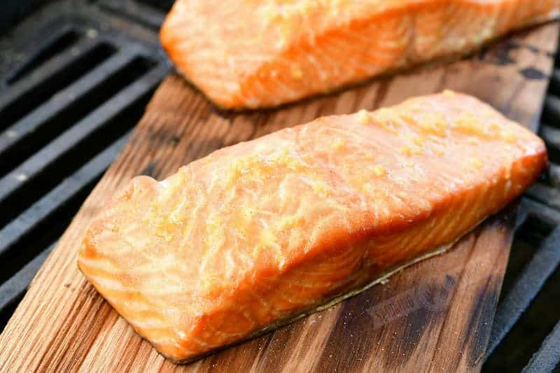 cooked salmon on a wood plank on a grill