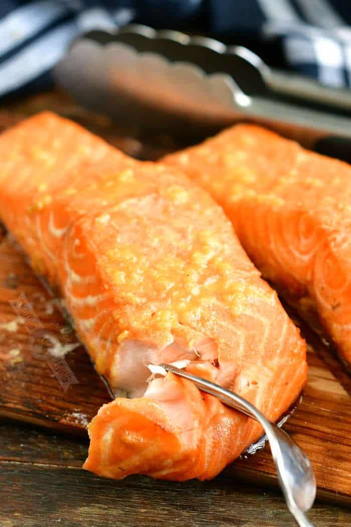 fork pulling apart a piece of cooked salmon on a wood plank