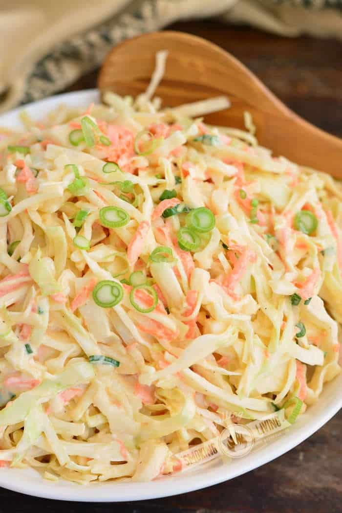 side view of coleslaw in a bowl with wooden spoon in the bowl