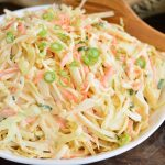 horizontal view of coleslaw in a bowl with a wooden spoon next to it