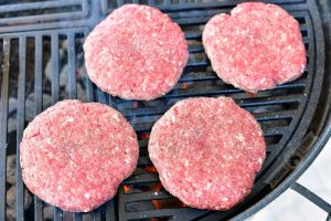 four uncooked burger patties on the grill