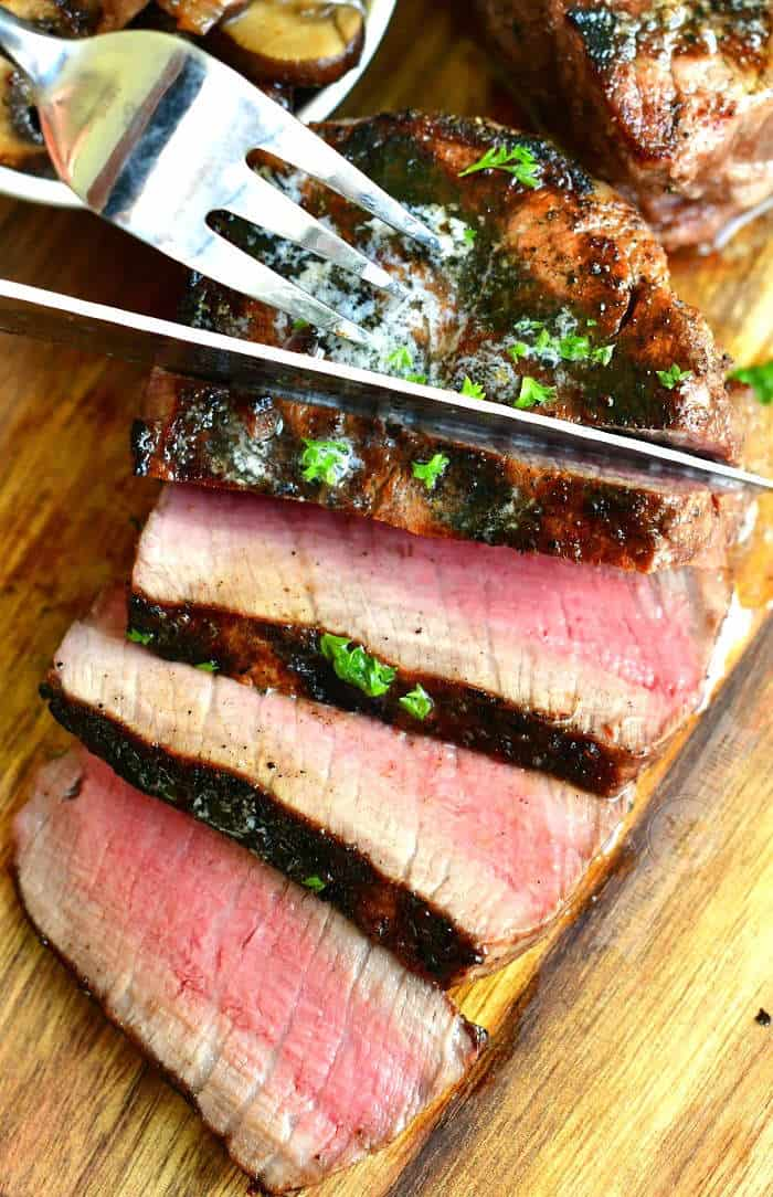 top view of slicing cooked filet mignon with a knife and some parsley sprinkled on top