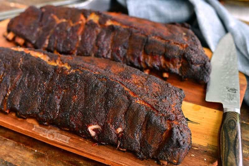 two racks of ribs on the wooden board right off the smoker with a knife and a towel next to it
