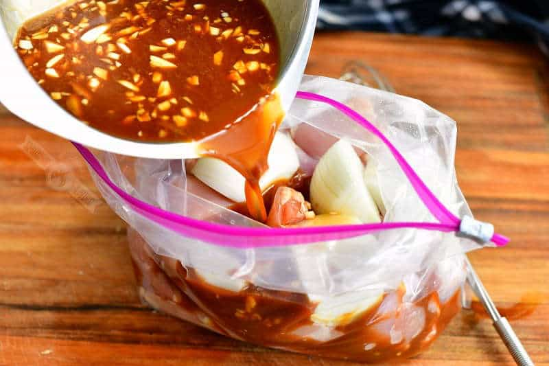 pouring teriyaki marinade into the bag with chicken and onions
