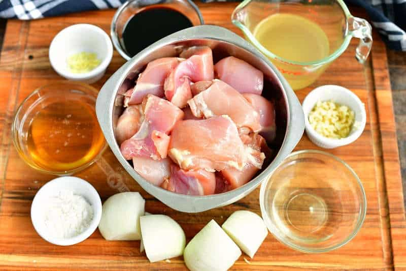 ingredients in bowls on a wooden cutting board including cut chicken meat, onions, corn starch, garlic, vinegar, honey, broth, soy sauce, and ginger