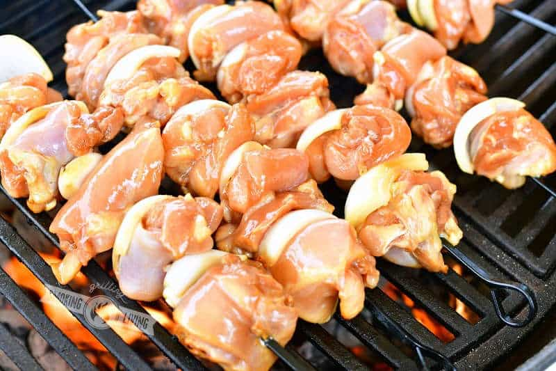 uncooked chicken and onions skewered on black skewers on the grill