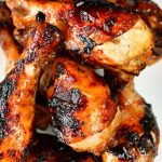top view of grilled chicken legs stacked on top of each other on a white plate