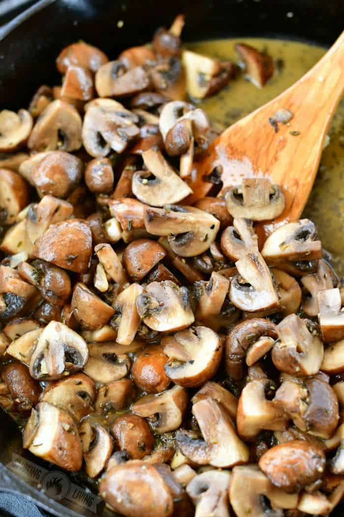 closeup of mushrooms in a cast iron skillet with a wooden spatula in the corner