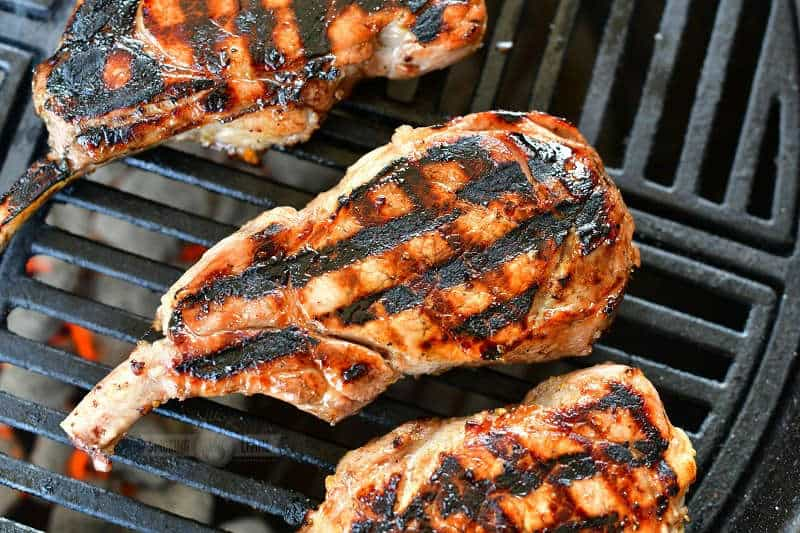 horizontal view of one pork chop in the center with grill marks in criss-cross and portions of two other pork chops visible