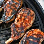 four grilled pork chops on the grill