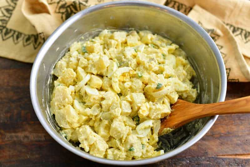mixing potato salad ingredients together in a metal mixing bowl with a light brown towel behind it