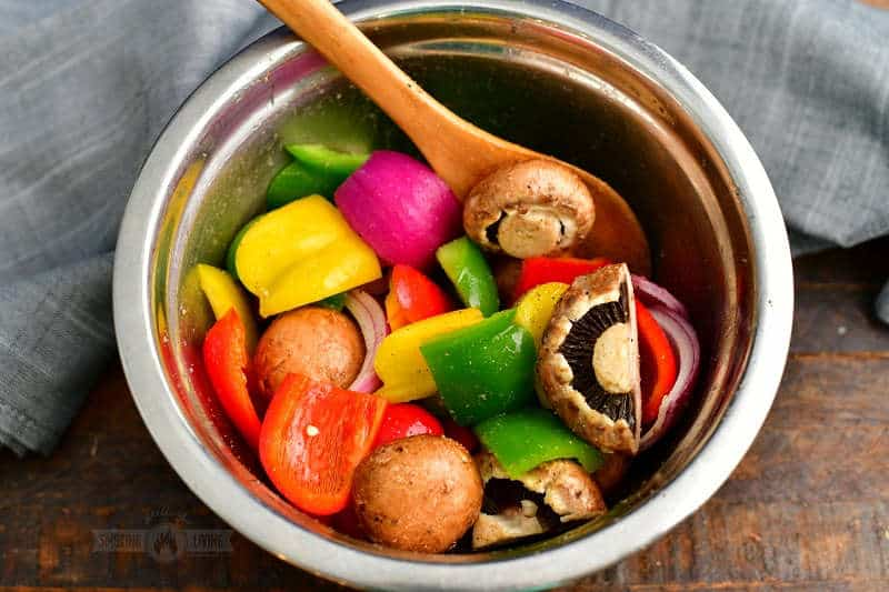 mixing bowl filled with cut vegetables like bell peppers, red onions, and mushrooms mixed with olive oil and seasoning