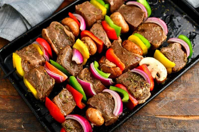 pieces of steak and vegetables skewered on four skewers on a black baking sheet