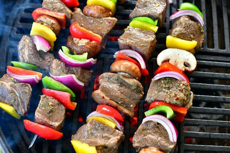 uncooked beef and vegetables on skewers on the grill