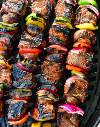 four long skewers with cooked steak pieces and vegetables skewered onto them on the grill