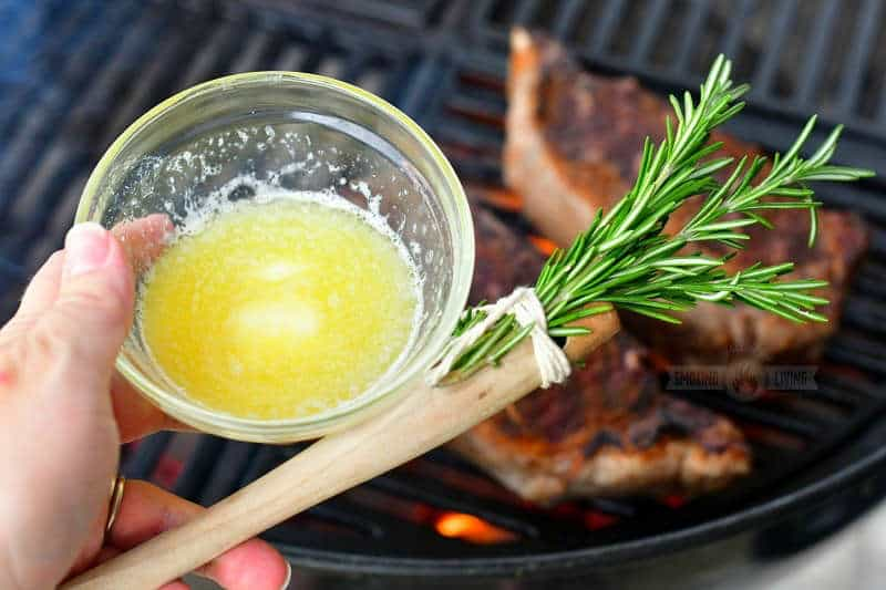 holding a small clear dish of melted butter and rosemary brush with steaks on the grill on the background