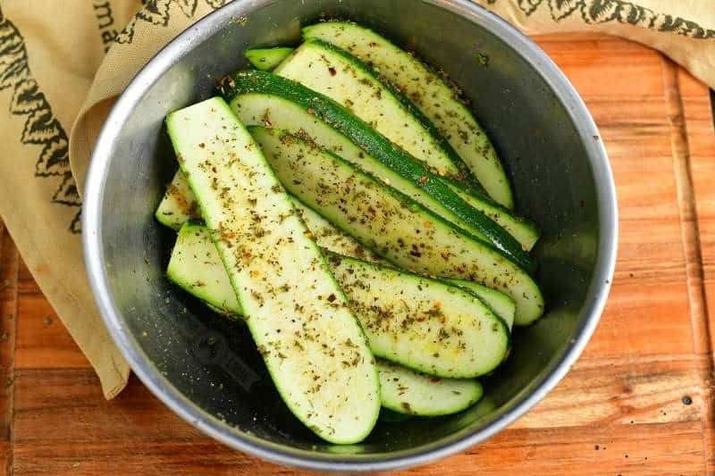 seasoned long zucchini slices in a mixing bowl on top of wooden cutting board with a brown towel around