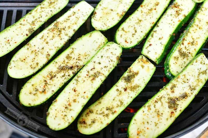 uncooked seasoned zucchini slices side by side on the grill