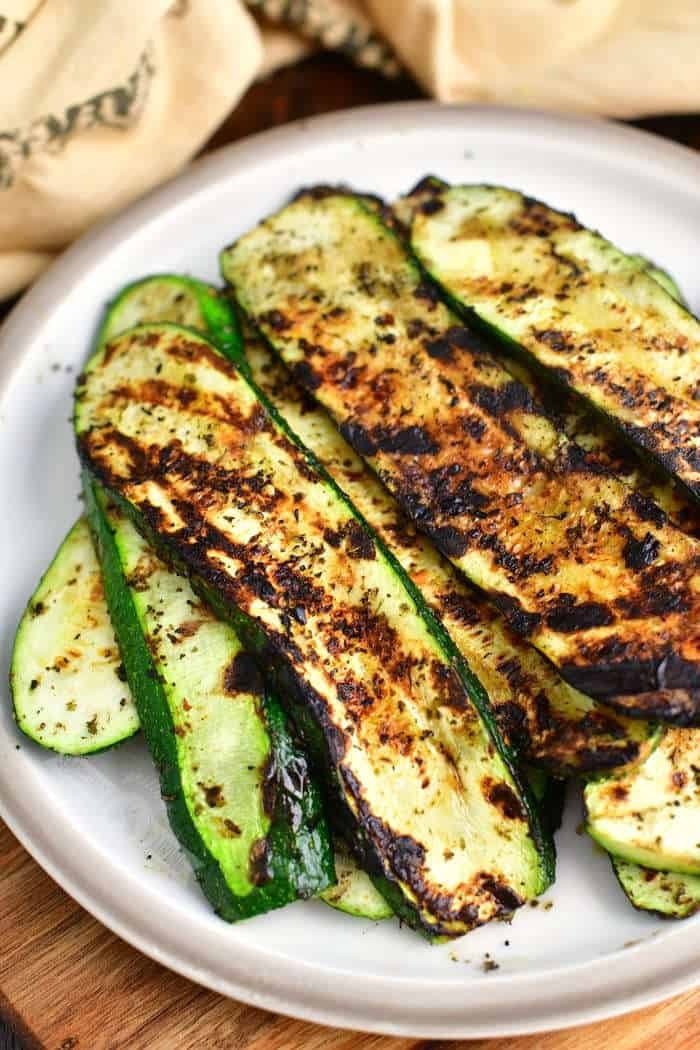 long slices of grilled zucchini on a plate with a light brown towel next to the plate