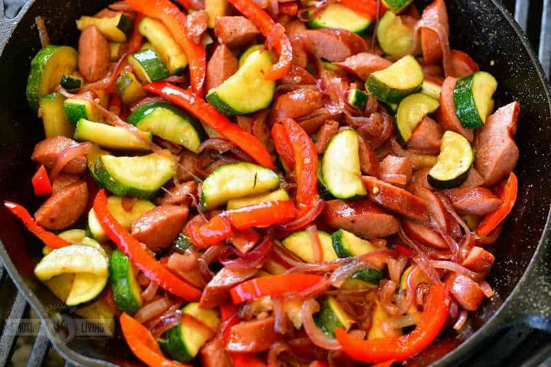 sausage, zucchini, red peppers and onion cooking in a cast iron skillet