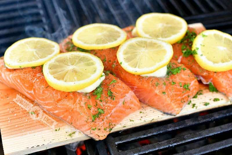 uncooked salmon fillets on a wooden plank with butter, herbs, and lemon slices on top