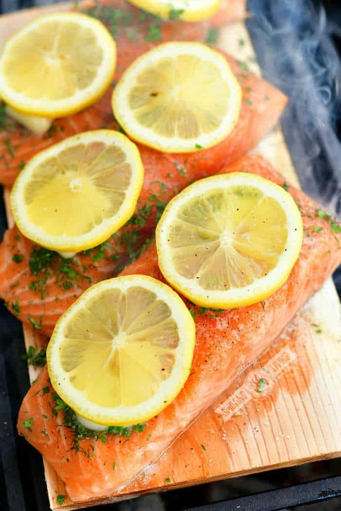 uncooked salmon fillets with lemon and herbs on top on a wooden plank