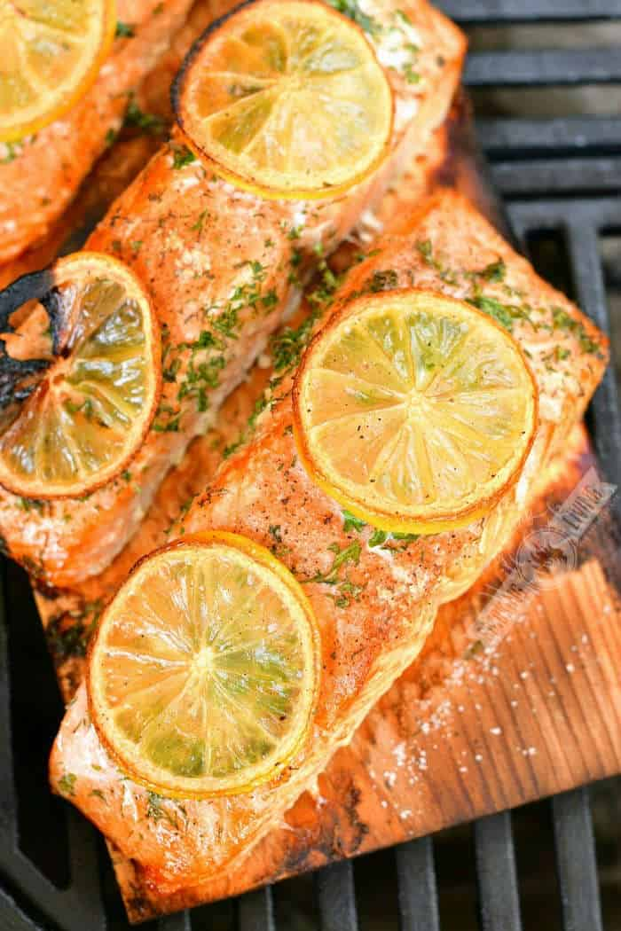 top view of cooked salmon pieces with lemon slices on top on the plank on the grill