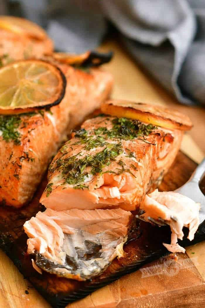 cooked salmon with herbs on top and some salmon flaked off on a fork