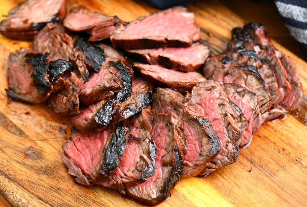 sliced grilled steak on a wooden cutting board