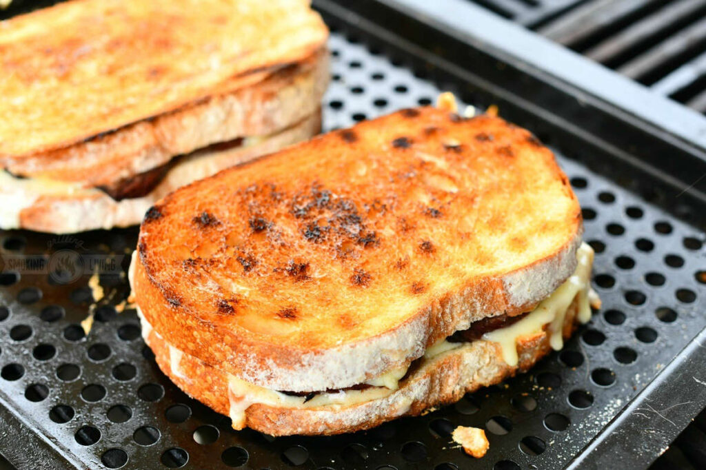 closeup of a full grilled cheese sandwich cooking on the grill on a tray