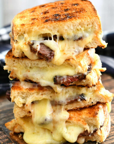 side view of 4 steak grilled cheese halves stacked on to of each other