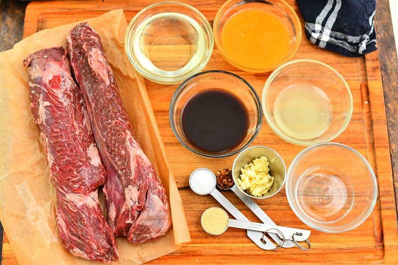 two hanger steaks and ingredients for the marinade laid out on a wood cutting board