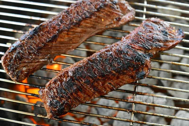 two long steaks cooking over charcoal on the grill grate